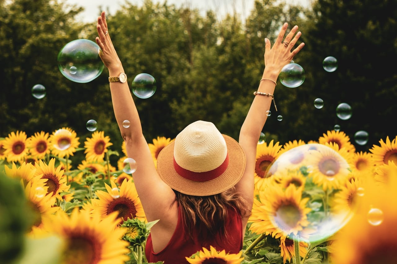 woman-in-field-of-sunflowers-with-bubbles